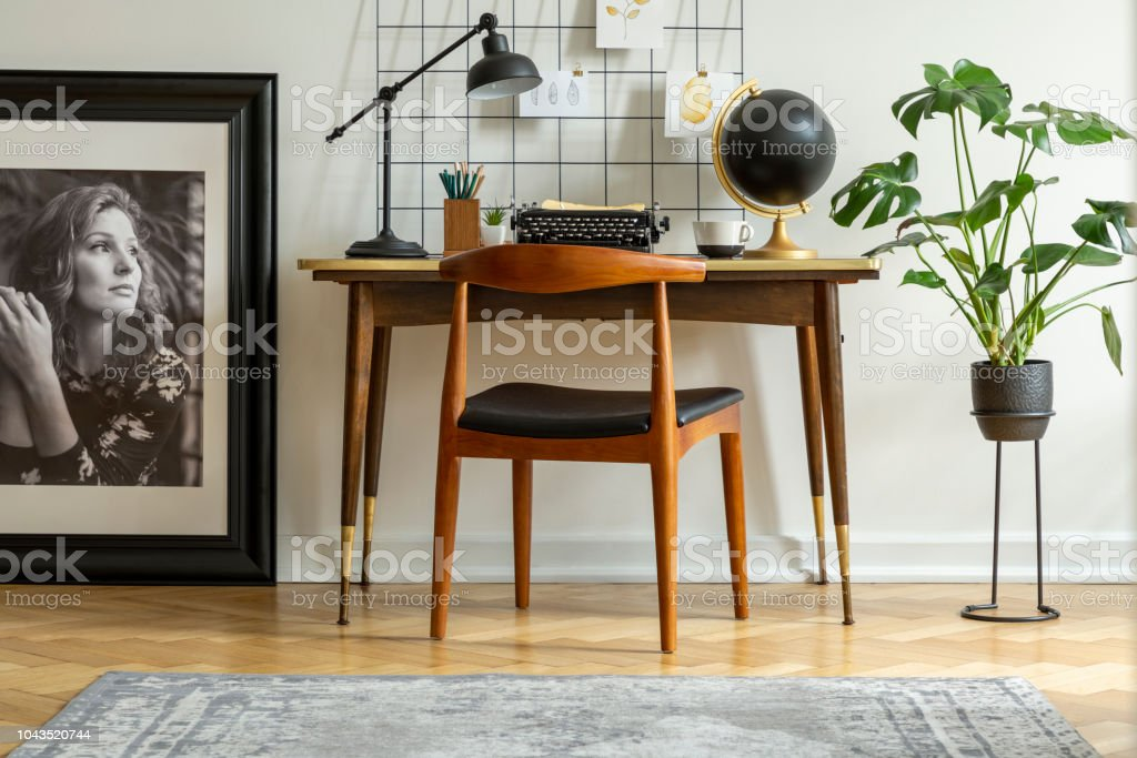 Mid-century modern chair with leather seat by a desk with an industrial lamp and a retro typewriter in a white home office interior stock photo