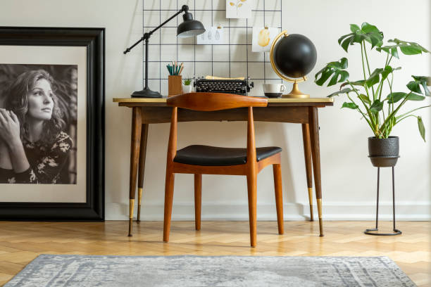 mid-century modern chair with leather seat by a desk with an industrial lamp and a retro typewriter in a white home office interior - midcentury design stock photos and pictures