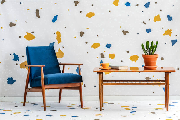 Mid-century modern, navy blue armchair and a retro wooden table in a white living room interior with lastrico pattern on the wall and floor. Real photo. stock photo