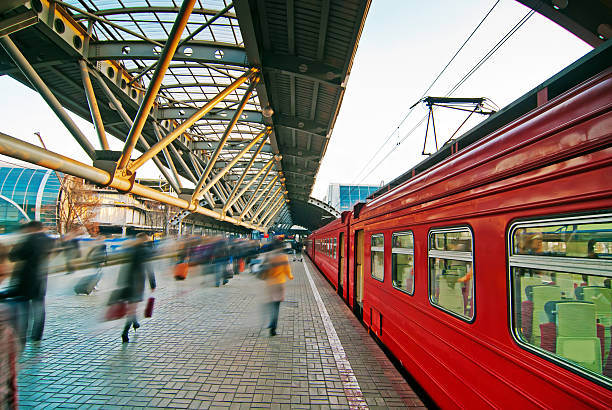 Midday on a sunny day at a train station Train station with red train and  blurred people. electric train stock pictures, royalty-free photos & images