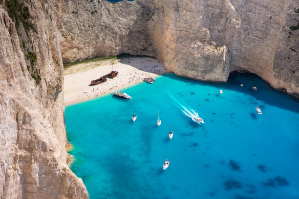 Mid-day photo of Shipwreck beach, Zakynthos island. Turquoise water and boats. stock photo