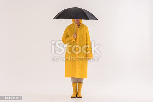 Middle adult woman in yellow raincoat and rain boots