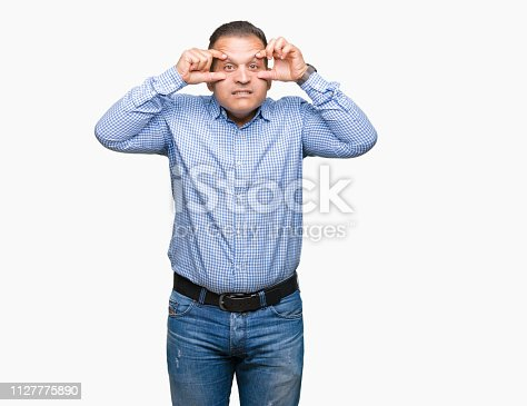 istock Middle age arab business man over isolated background Trying to open eyes with fingers, sleepy and tired for morning fatigue 1127775890