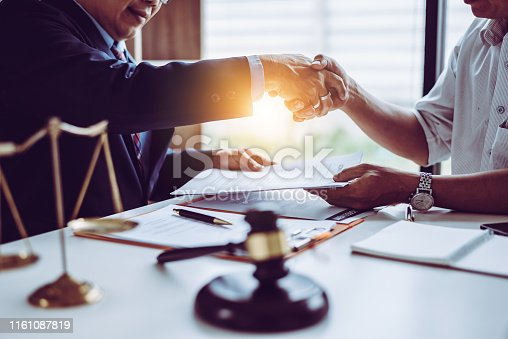 istock Middle age Asian partner lawyers attorneys shaking hands after discussing a contract agreement done. 1161087819