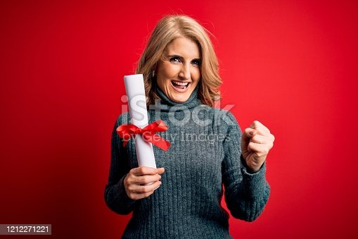 1175468850istockphoto Middle age beautiful blonde student woman holding university graduate diploma screaming proud and celebrating victory and success very excited, cheering emotion 1212271221