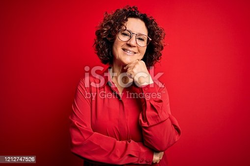 Middle age beautiful curly hair woman wearing casual shirt and glasses over red background looking confident at the camera smiling with crossed arms and hand raised on chin. Thinking positive.