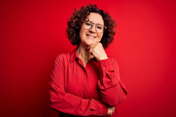 Middle age beautiful curly hair woman wearing casual shirt and glasses over red background looking confident at the camera smiling with crossed arms and hand raised on chin. Thinking positive. Middle age beautiful curly hair woman wearing casual shirt and glasses over red background looking confident at the camera smiling with crossed arms and hand raised on chin. Thinking positive. red shirt stock pictures, royalty-free photos & images