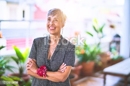 Middle age beautiful grey-haired woman wearing dress and bandana on wrist smiling happy and confident standing with a smile on face at terrace