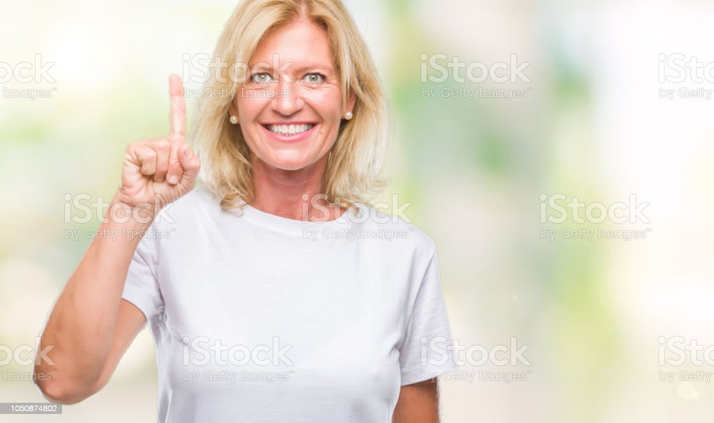 Middle age blonde woman over isolated background showing and pointing up with finger number one while smiling confident and happy. stock photo
