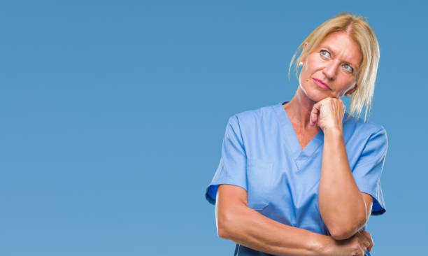 middle age blonde woman wearing doctor nurse uniform over isolated background with hand on chin thinking about question, pensive expression. smiling with thoughtful face. doubt concept. - stupidblonde stock pictures, royalty-free photos & images