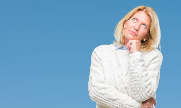 middle age blonde woman wearing winter sweater over isolated background with hand on chin thinking about question, pensive expression. smiling with thoughtful face. doubt concept. - stupidblonde stock pictures, royalty-free photos & images