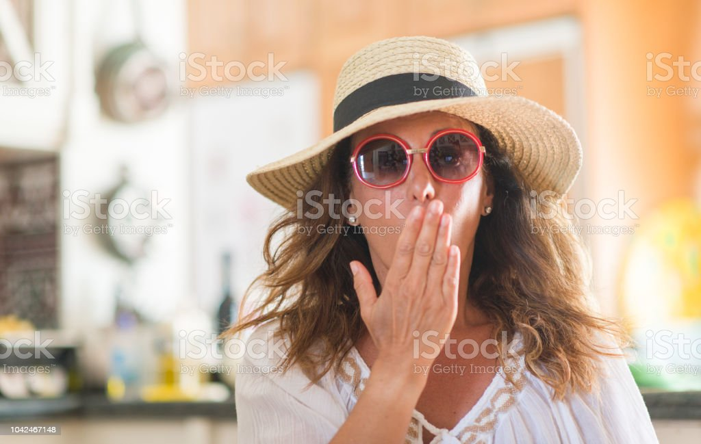 Middle age brunette woman wearing summer hat on vacations cover mouth...