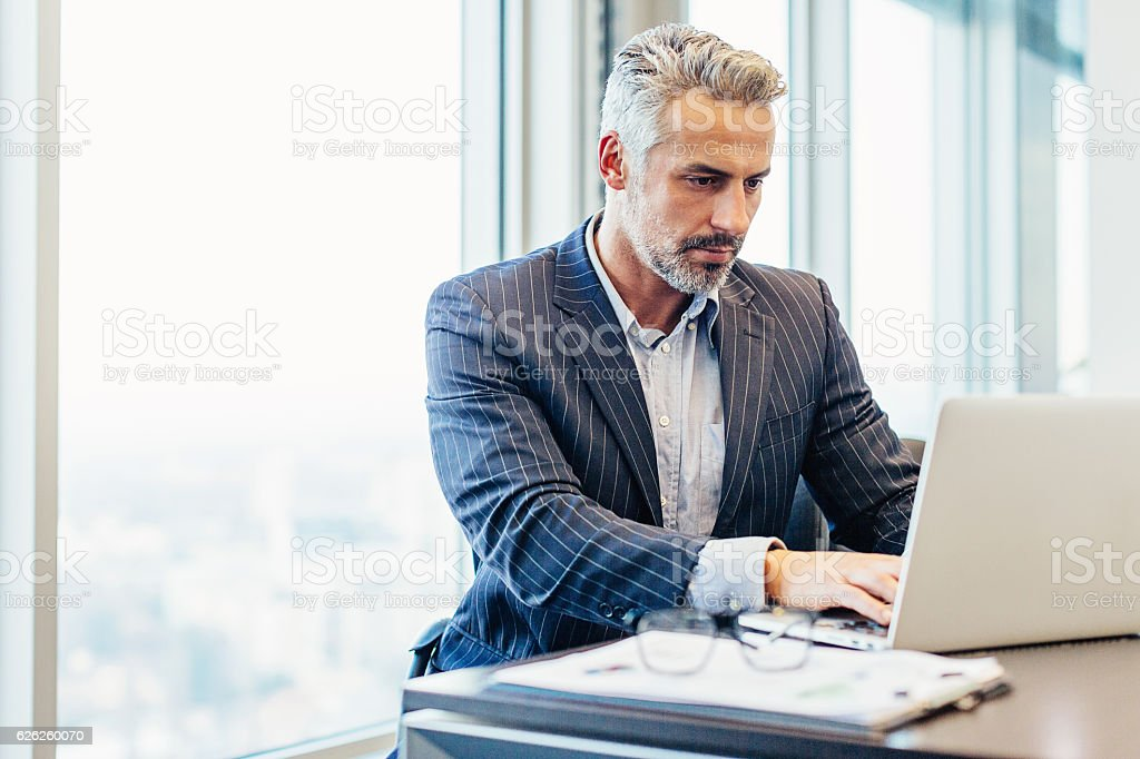 Middle age businessman in the office stock photo