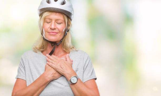 mittelalter-kaukasischen radfahrer frau tragen schutzhelm über isolierte hintergrund lächelnd mit händen auf brust mit geschlossenen augen und dankbar geste auf gesicht. gesundheitskonzept. - die wahrheit tut weh stock-fotos und bilder