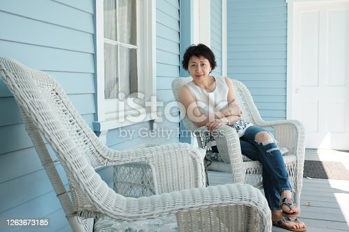 Middle age Chinese woman sitting at the porch in casual pose