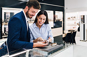 Beautiful couple enjoying in shopping at modern jewelry store while trying out and buying watches.