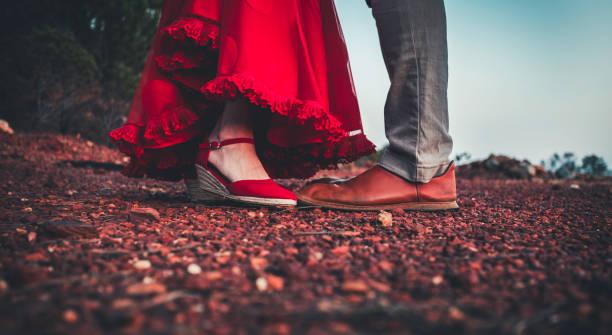 mittleres ehepaar mit füßen in roten lederschuhen und rotem ruffelkleid - bräutigam jeans stock-fotos und bilder