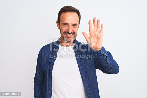 Middle age handsome man wearing blue denim shirt standing over isolated white background Waiving saying hello happy and smiling, friendly welcome gesture