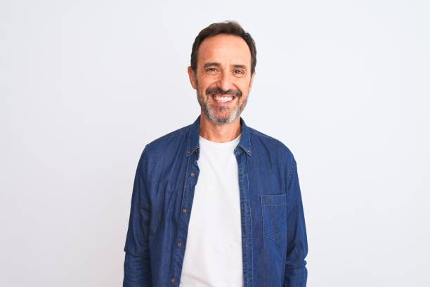 Middle age handsome man wearing blue denim shirt standing over isolated white background with a happy and cool smile on face. Lucky person. stock photo