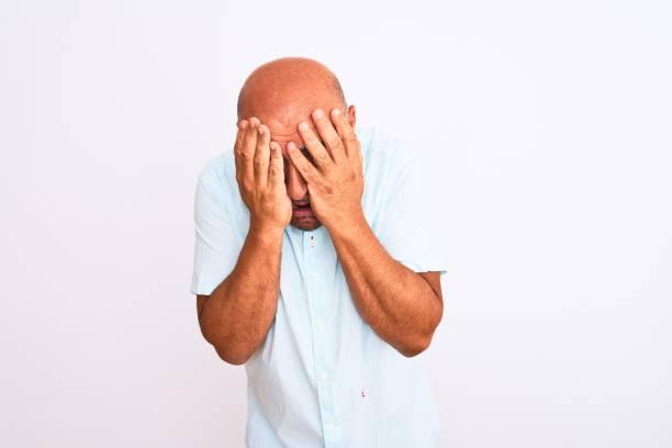 hombre guapo de la mediana edad con camisa casual de pie sobre fondo blanco aislado con expresión triste cubriendo la cara con las manos mientras llora. concepto de depresión. - vergüenza fotografías e imágenes de stock