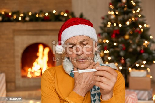 Middle age handsome man wearing Santa claus hat, scarf and jumper, posing indoor on background of fireplace and xmas tree, suffering fro m illness and fever, holds thermometer in hands.