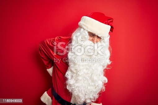 istock Middle age handsome man wearing Santa costume standing over isolated red background Suffering of backache, touching back with hand, muscular pain 1185949003