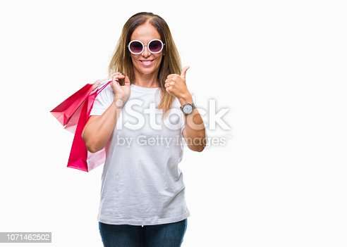 Middle age hispanic woman holding shopping bags on sales over isolated background happy with big smile doing ok sign, thumb up with fingers, excellent sign