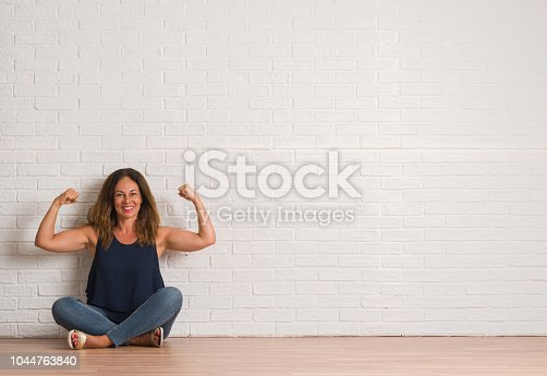 istock Middle age hispanic woman sitting on the floor over white brick wall showing arms muscles smiling proud. Fitness concept. 1044763840