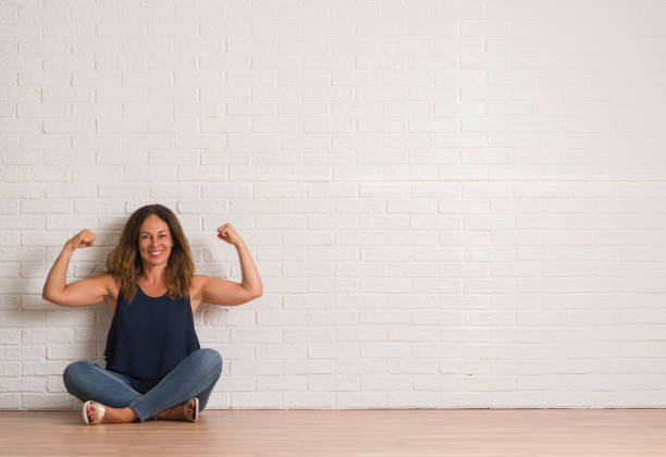 middle age hispanic woman sitting on the floor over white brick wall showing arms muscles smiling proud. fitness concept. - muscolo foto e immagini stock