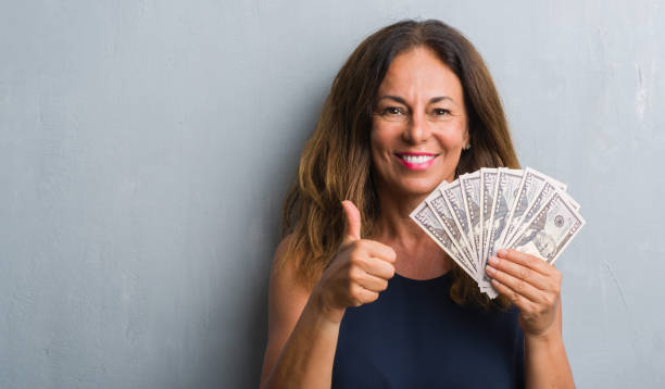 middle age hispanic woman standing over grey grunge wall holding dollars happy with big smile doing ok sign, thumb up with fingers, excellent sign - dollar bill стоковые фото и изображения