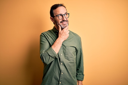 Middle age hoary man wearing casual green shirt and glasses over isolated yellow background with hand on chin thinking about question, pensive expression. Smiling with thoughtful face. Doubt concept.