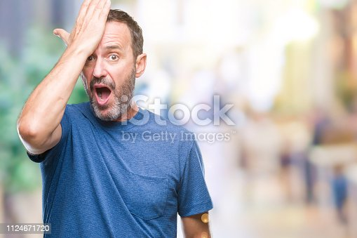 istock Middle age hoary senior man over isolated background surprised with hand on head for mistake, remember error. Forgot, bad memory concept. 1124671720