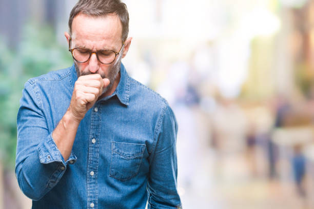middle age hoary senior man wearing glasses over isolated background feeling unwell and coughing as symptom for cold or bronchitis. healthcare concept. - tossire foto e immagini stock
