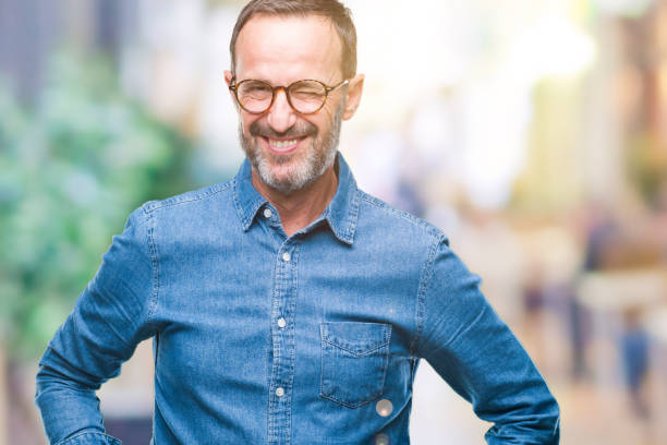 middle age hoary senior man wearing glasses over isolated background winking looking at the camera with sexy expression, cheerful and happy face. - blinking stock pictures, royalty-free photos & images