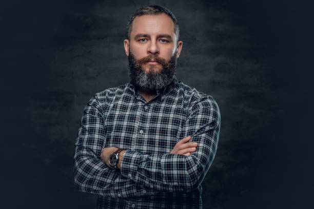 Middle age male in plaid shirt. Portrait of serious middle age bearded male dressed in plaid flannel shirt over grey background. plaid shirt stock pictures, royalty-free photos & images