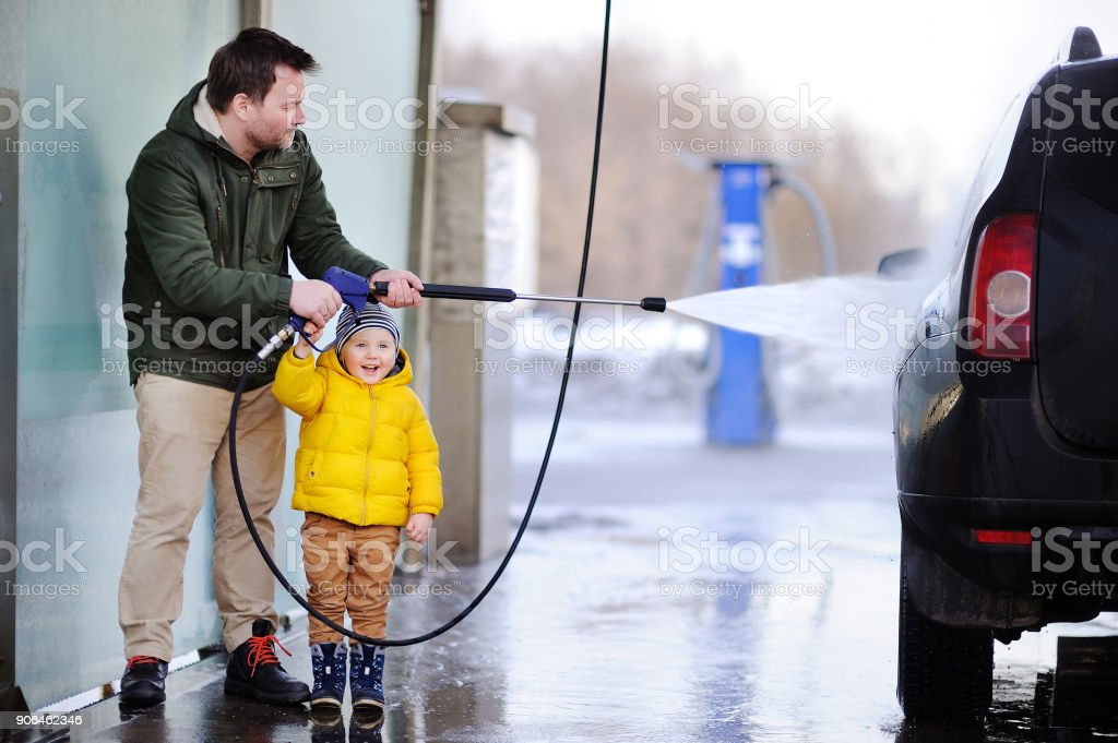 Middle age man and his little son washing a car on a carwash stock photo