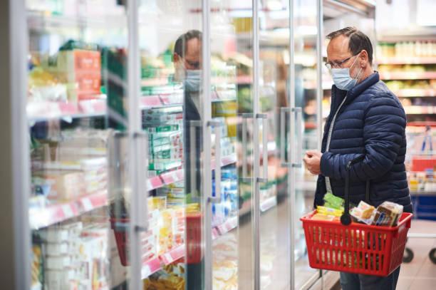 Mittleres Alter Mann kaufen Lebensmittel in Lebensmittelgeschäft, trägt medizinische Maske – Foto