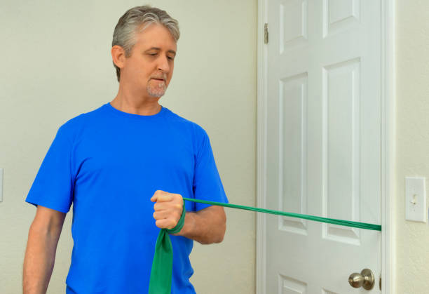 Middle age man doing shoulder surgery physical therapy with a resistance rubber band at his home stock photo