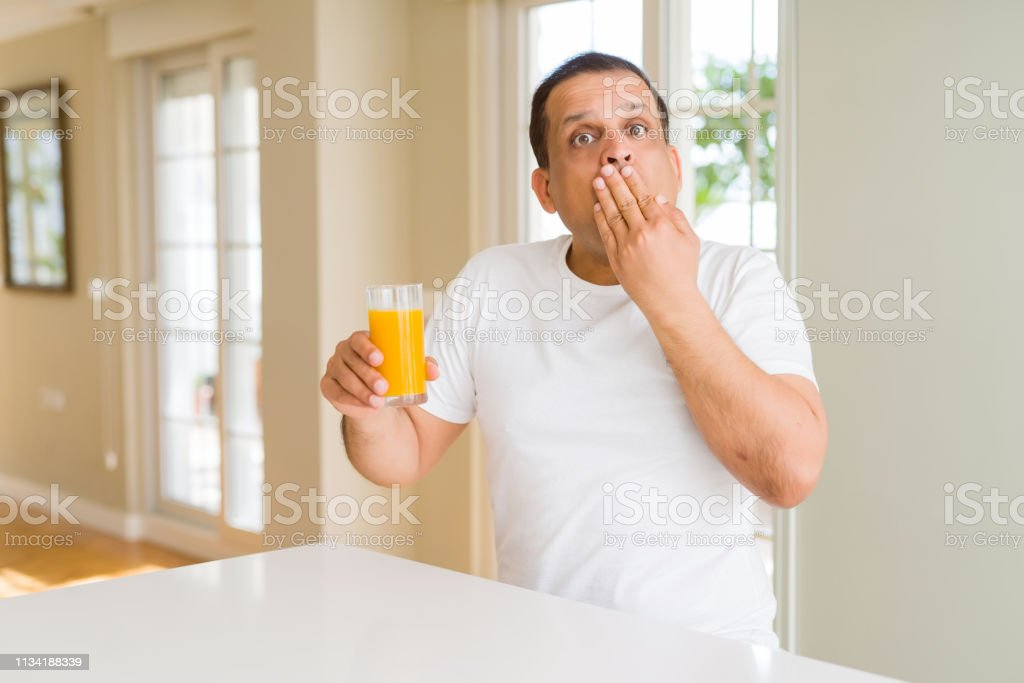 Middle age man drinking a glass of orange juice at home cover mouth...