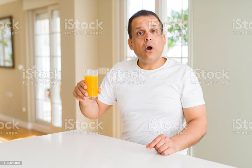 Middle Age Man Drinking A Glass Of Orange Juice At Home