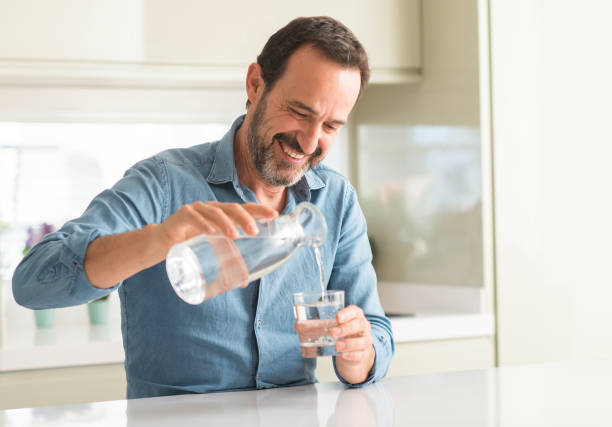 Middle age man drinking a glass of water with a happy face standing and smiling with a confident smile showing teeth Middle age man drinking a glass of water with a happy face standing and smiling with a confident smile showing teeth drinking water stock pictures, royalty-free photos & images