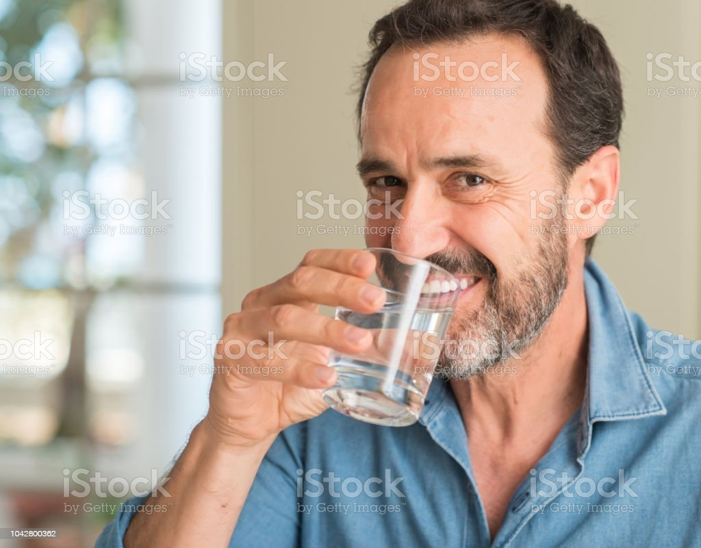 Middle age man drinking a glass of water with a happy face standing...