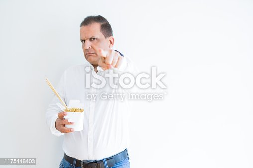 Middle age man eating asian noodles from take away carton pointing with finger to the camera and to you, hand sign, positive and confident gesture from the front