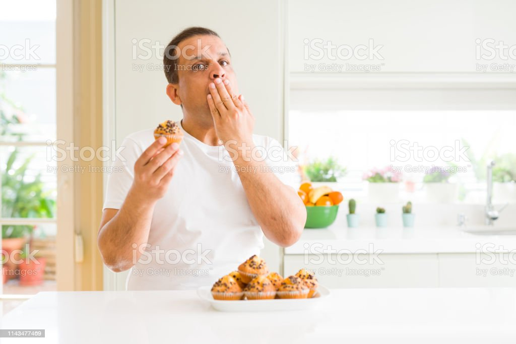 Middle age man eating chocolate chip muffins at home cover mouth with...