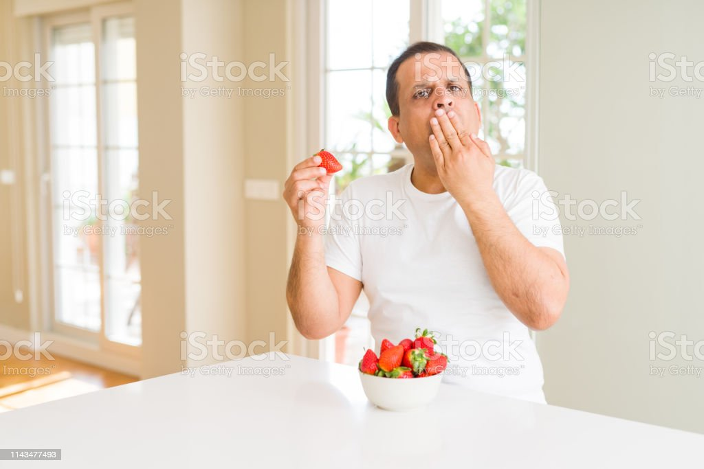 Middle age man eating strawberries at home cover mouth with hand...
