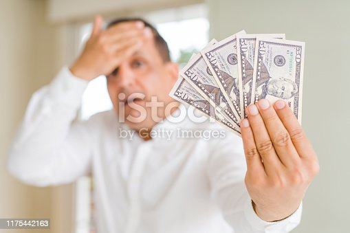 Middle age man holding bunch of dollars stressed with hand on head, shocked with shame and surprise face, angry and frustrated. Fear and upset for mistake.