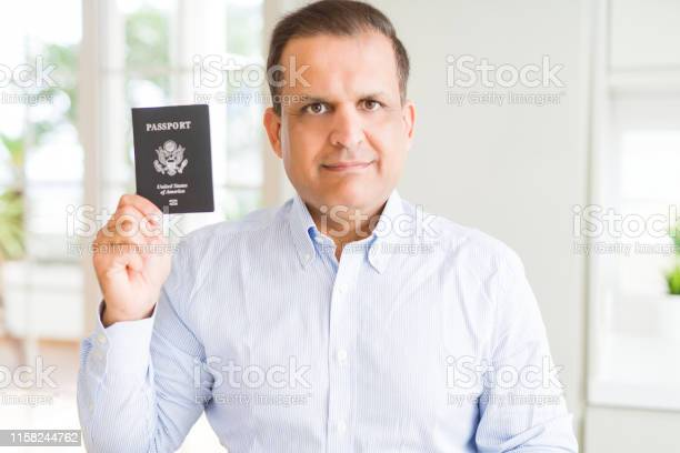 Middle age man holding holding passport of united states with a on picture id1158244762?b=1&k=6&m=1158244762&s=612x612&h=2 v4oqkzm3r0wzm0qqoud dtzyqlfo 0etxhdbsdke8=