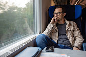 Middle age man looking out of the window of train. Passenger during travel by high speed express train, Europe