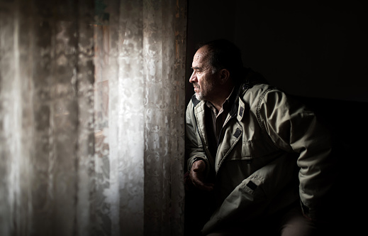 istock Middle Age Man looking Through Window 1136925515