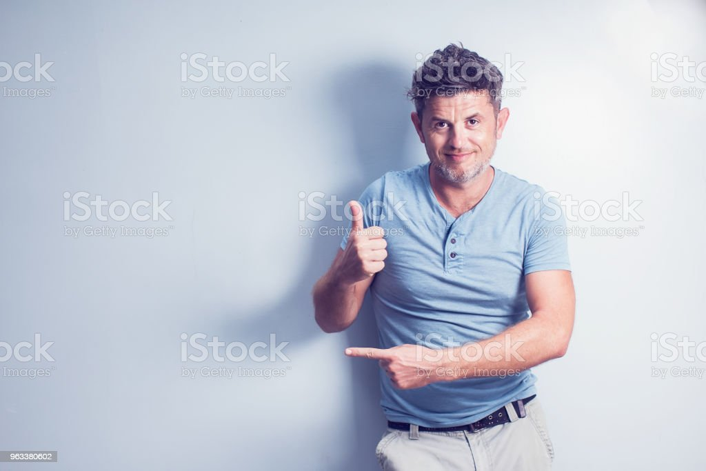 Middle age man smiling broadly showing thumbs up gesture to camera, expression of like and approval isolated over blue background - Zbiór zdjęć royalty-free (Blond włosy)
